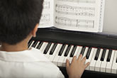 Boy playing a piano keyboard