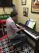 Student playing a piano keyboard