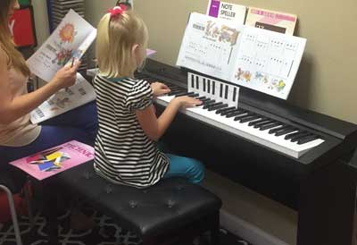 Girl playing keyboard under eyes of instructor